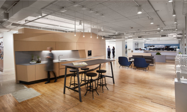 An office interior with an angular lightwood partition, and various furnishings such as a long black counter.