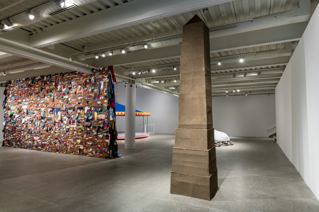 Gallery with obelisk sculpture, brick wall with wedged colorful garments, and a carousel in the background