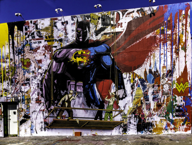 A Mr. Brainwash mural showing a man painting a mural of Batman and Superman mashed together