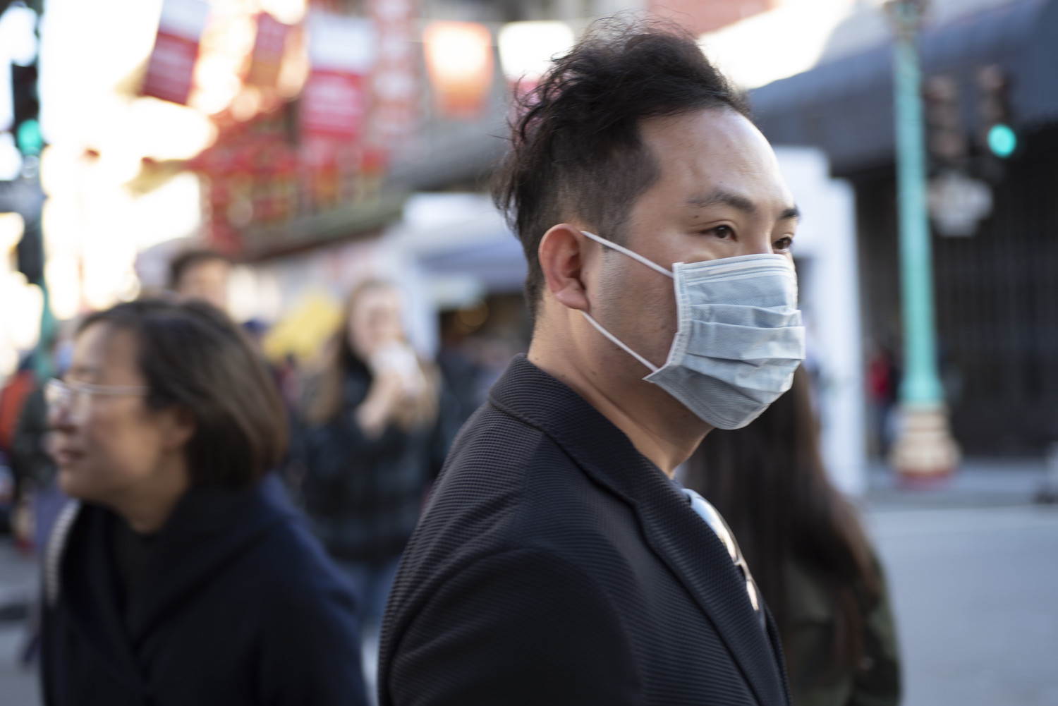 a man on the street wearing a respirator mask. Many popular events have been rescheduled due to coronavirus