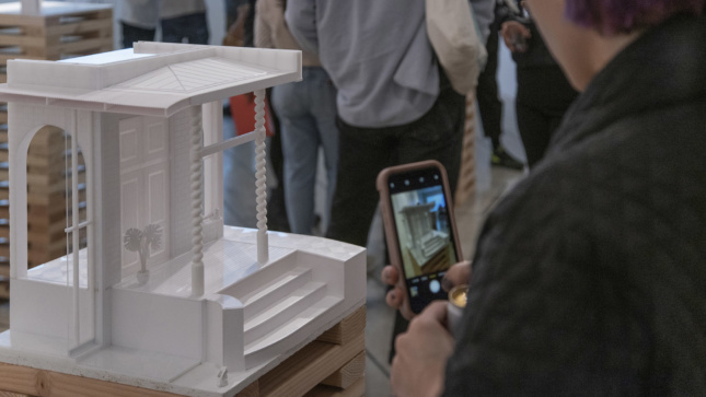A person pointing a smart phone at a model of a facade