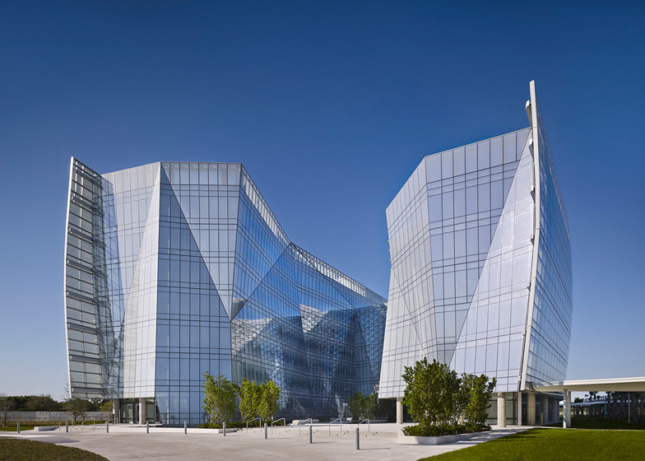 Exterior view of sharply shaped glass building with angular volumes