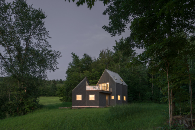 Photo of a Vermont cabin at dusk set against a green landscape