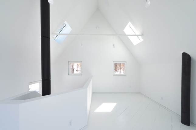 Interior of a white cabin with black pipes running through it