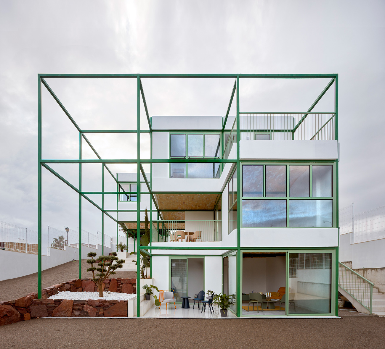 A home with a green metal grid surrounding it, designed by Space Popular