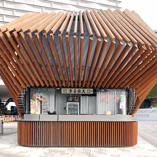 A wooden kiosk topped with an array of wooden elements.