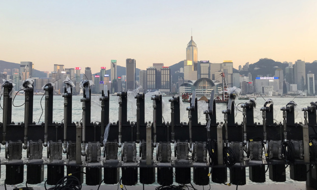 An array of robotic armatures in front of Hong Kong's harbor with the skyline in view.