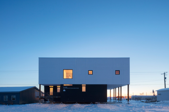 A boxy building in the snow with minimal window coverage