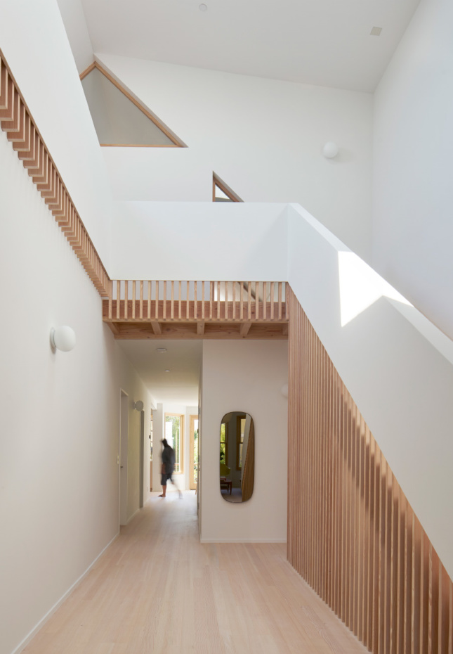 Interior of a white home with timber stairs, designed by an Emerging Voices winner