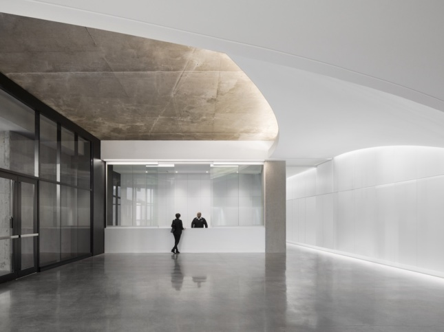 the main entrance at Montreal's renovated Olympic Tower, showing swooping white ceilings meeting exposed concrete slab