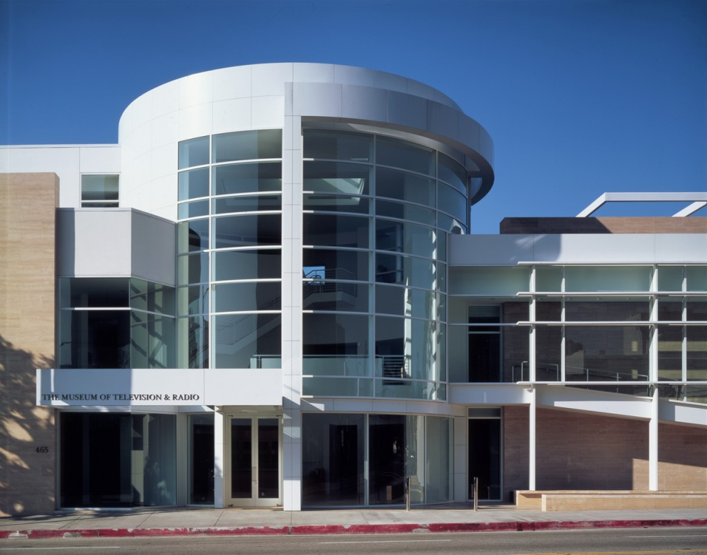 A round, three-story white building with a glazed central atrium