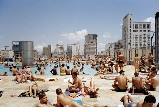 People crowding in and around a rooftop pool with skyscrapers visible in background