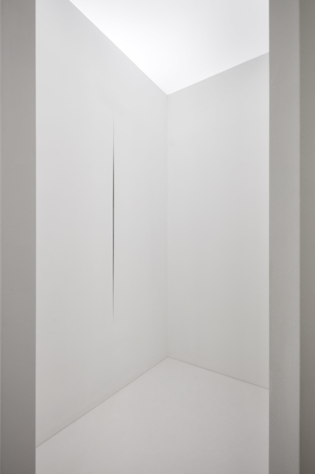 all-white room with a cut in the wall designed by Lucio Fontana