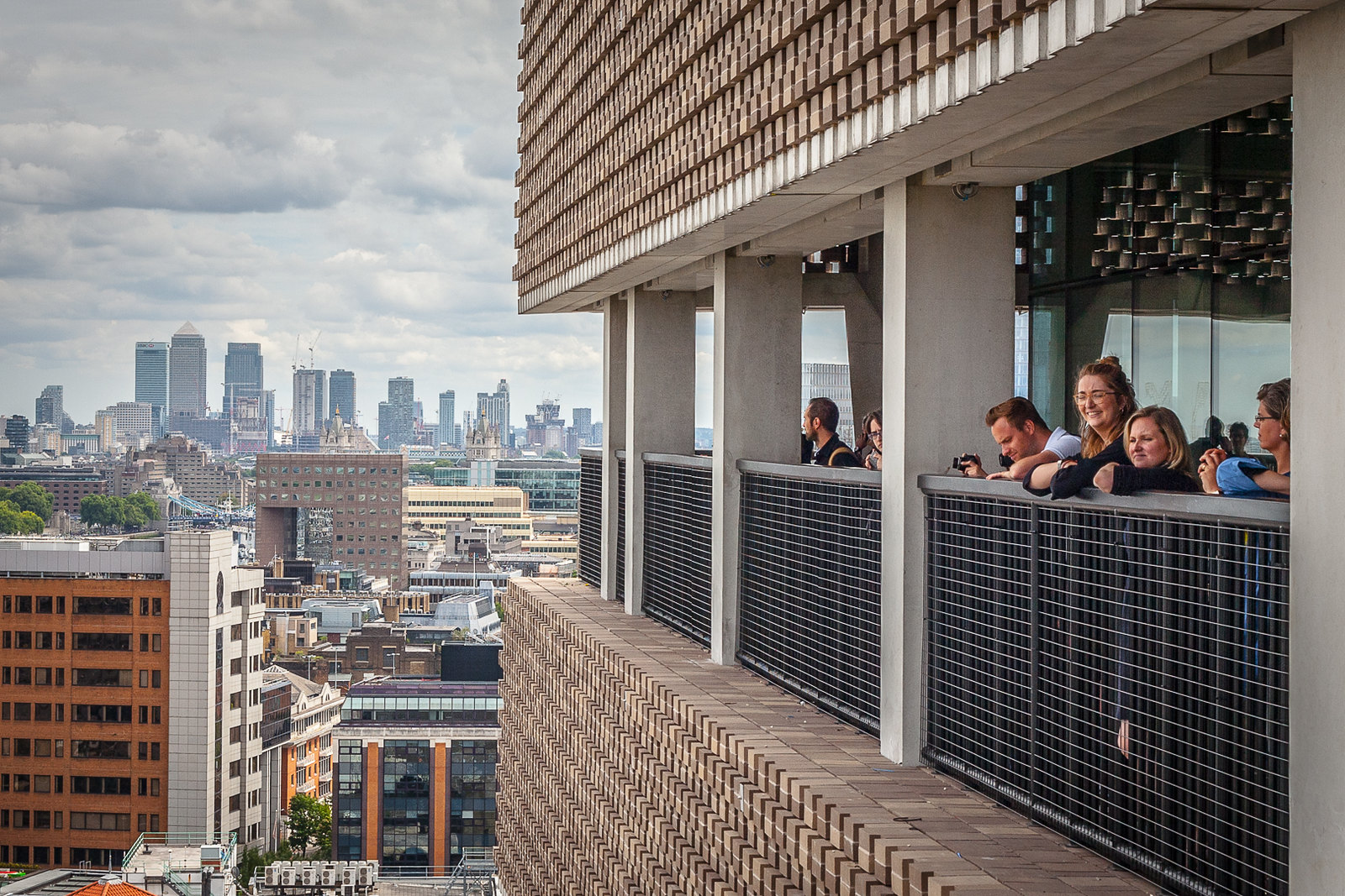 Balcony views at the Tate Modern in London, as people hang over the edge of a railing