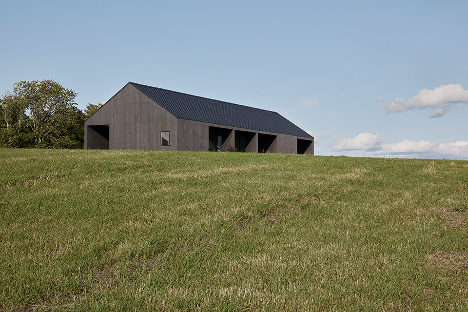 A long, barn-like house in a field