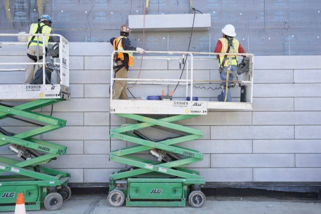 Construction image of concrete installation of The Glenstone Museum, with men on a scissorlift