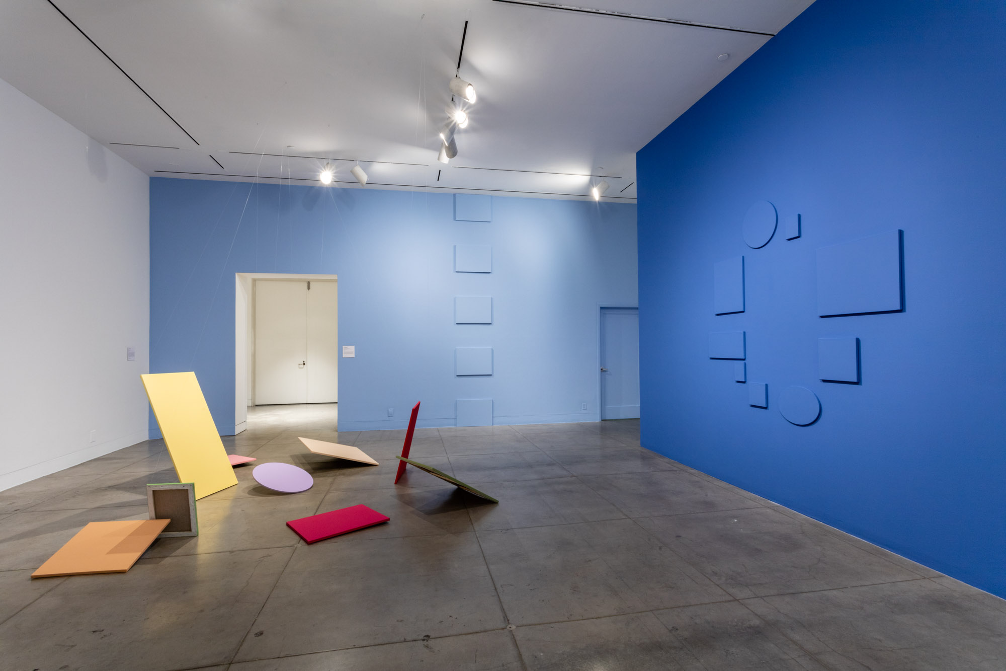 Interior of a gallery with blue walls covered in Claude Rutault paintings