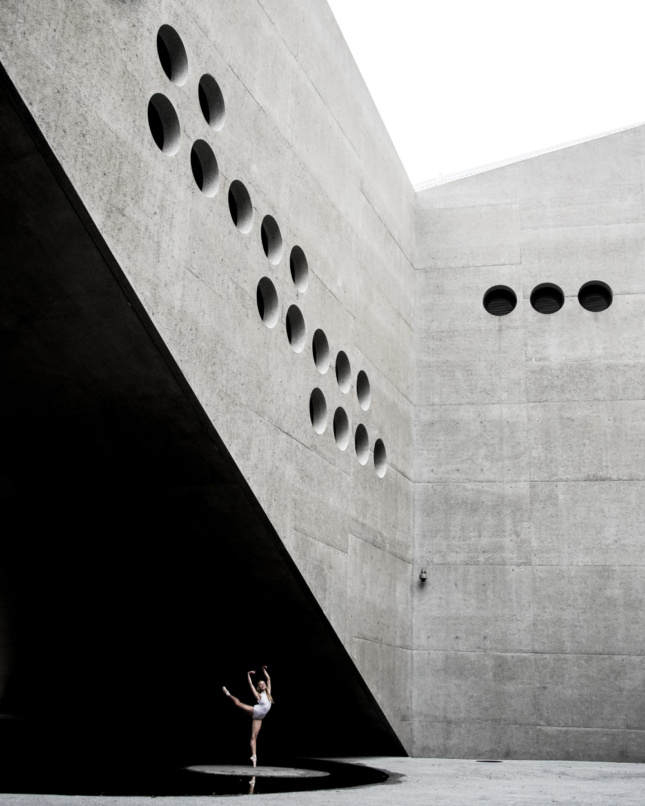 A dancer silhouetted below an upturned concrete corner