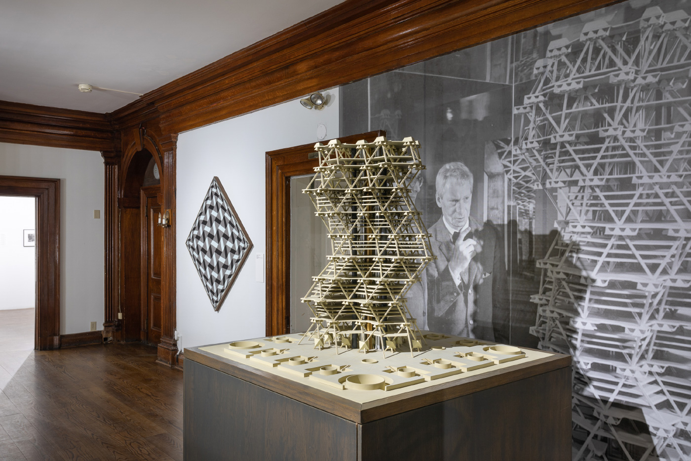 Interior exhibition shot of a twisting wooden tower, on view in Invisible City