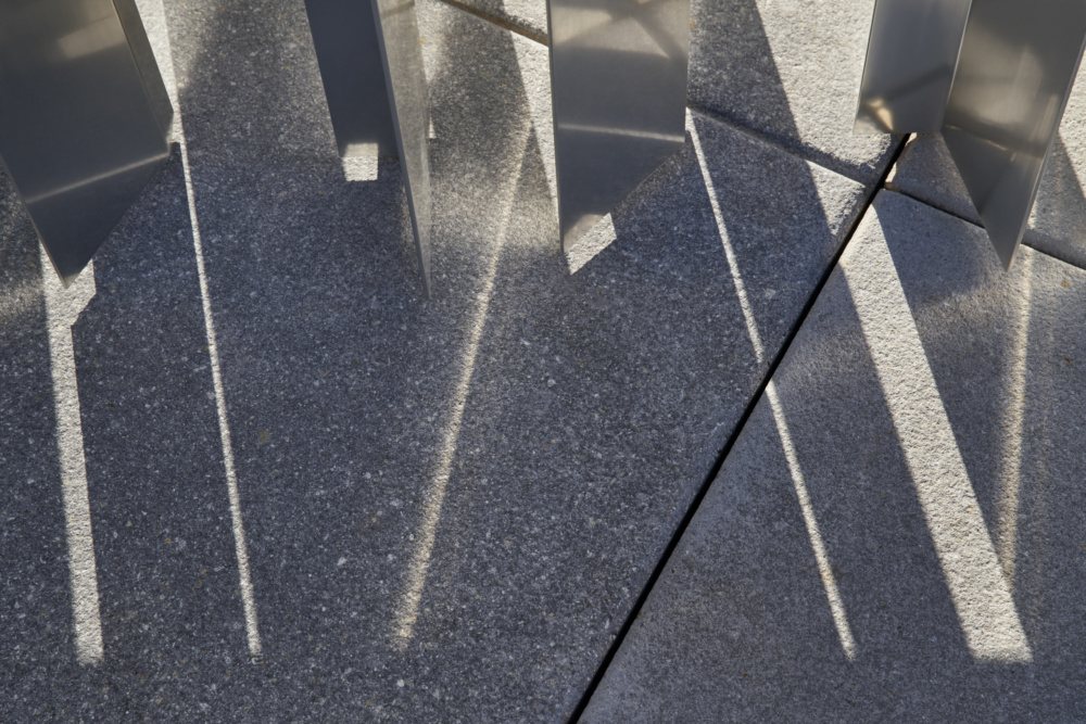 Detail of reflected light on facade bouncing off onto pavement