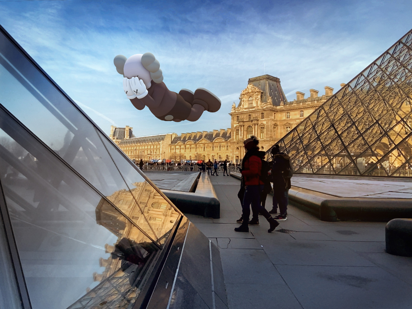 A KAWS bear floating above buildings and two people