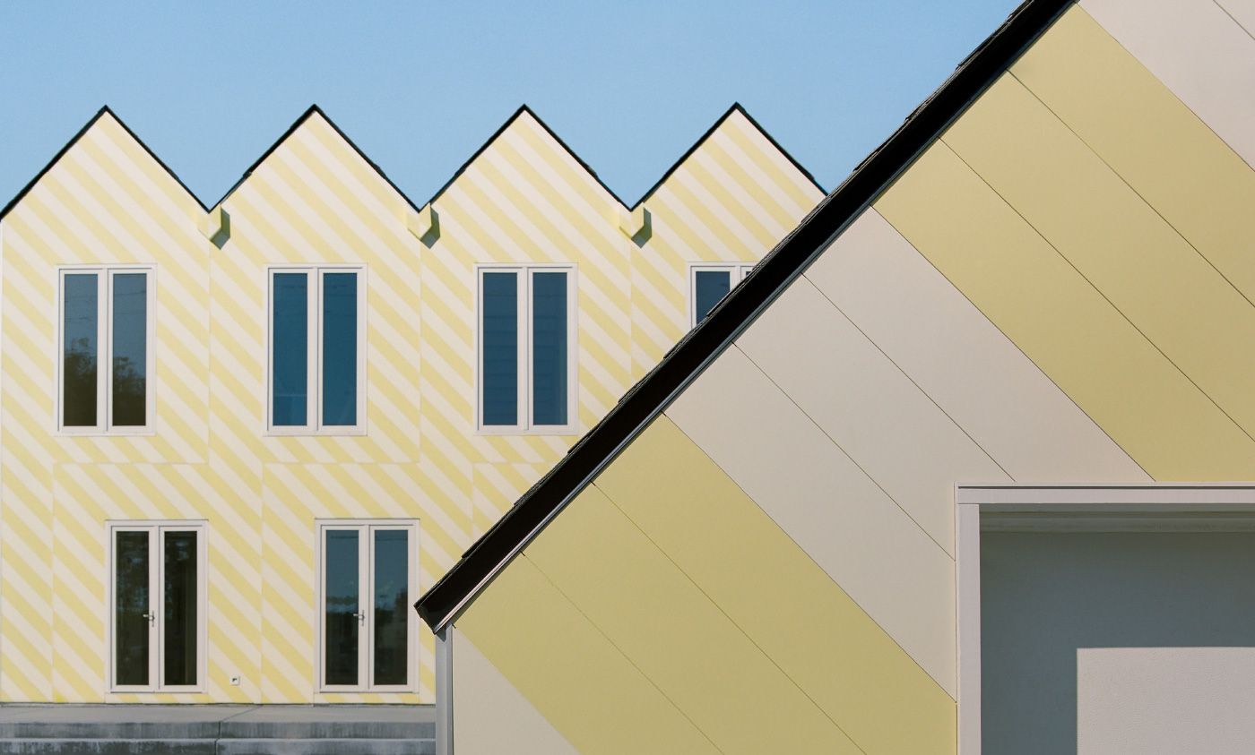 Exterior of a gabled house with yellow front designed by Independent Architecture