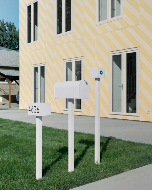 Mailboxes in front of a yellow home designed by Independent Architecture