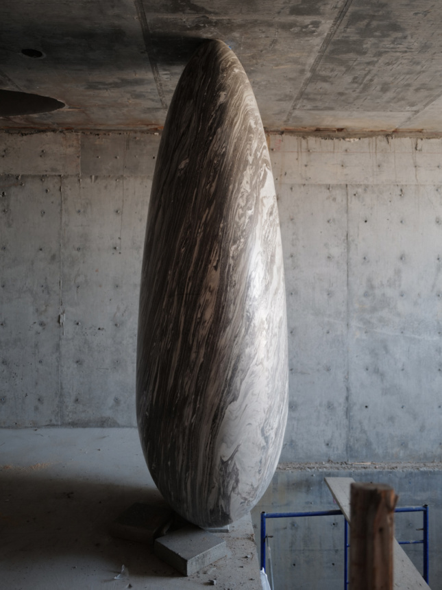 Photo of a tall oblong stone spanning from the floor to the ceiling