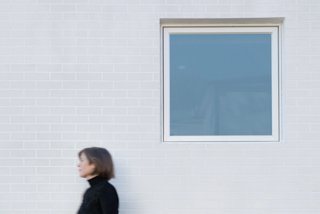 Exterior of a white house with Jennifer Bonner in front of the window