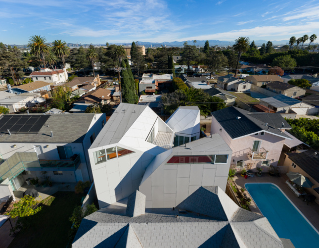 An aerial view of a white peaked home turned inward