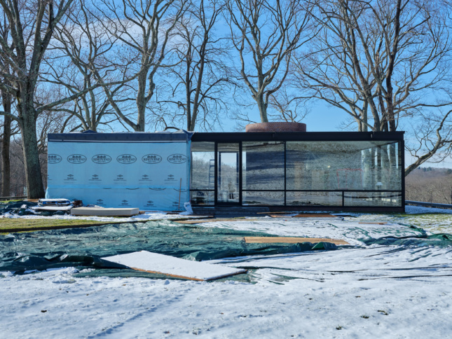 A winter photo of Philip Johnson's Glass House, half covered in tarps