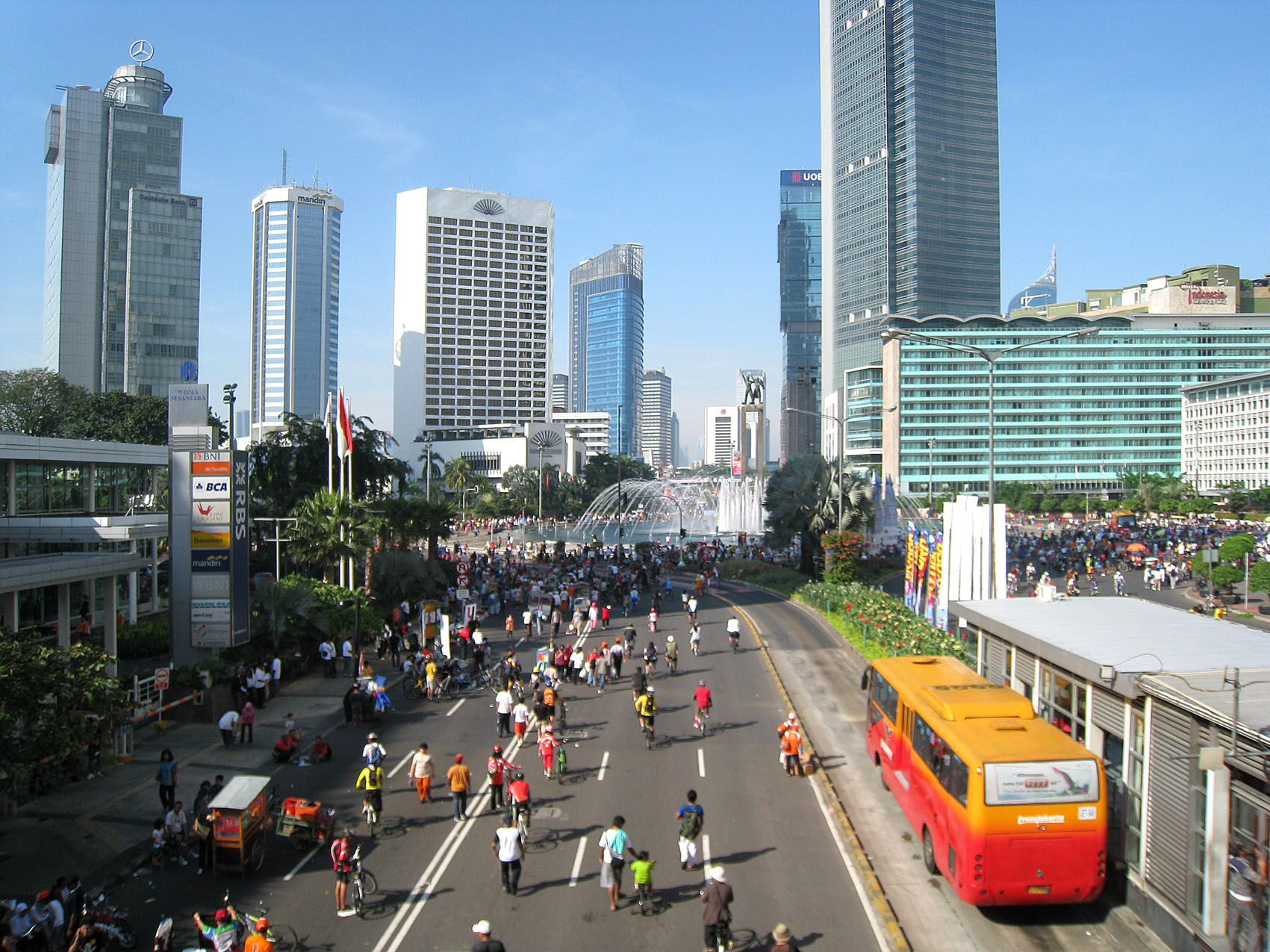 People on street with skyscrapers in the distance; Jakarta, Indonesia