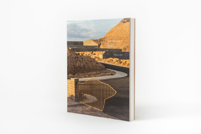 Cover of a book with a big front gate leading to a mountain path