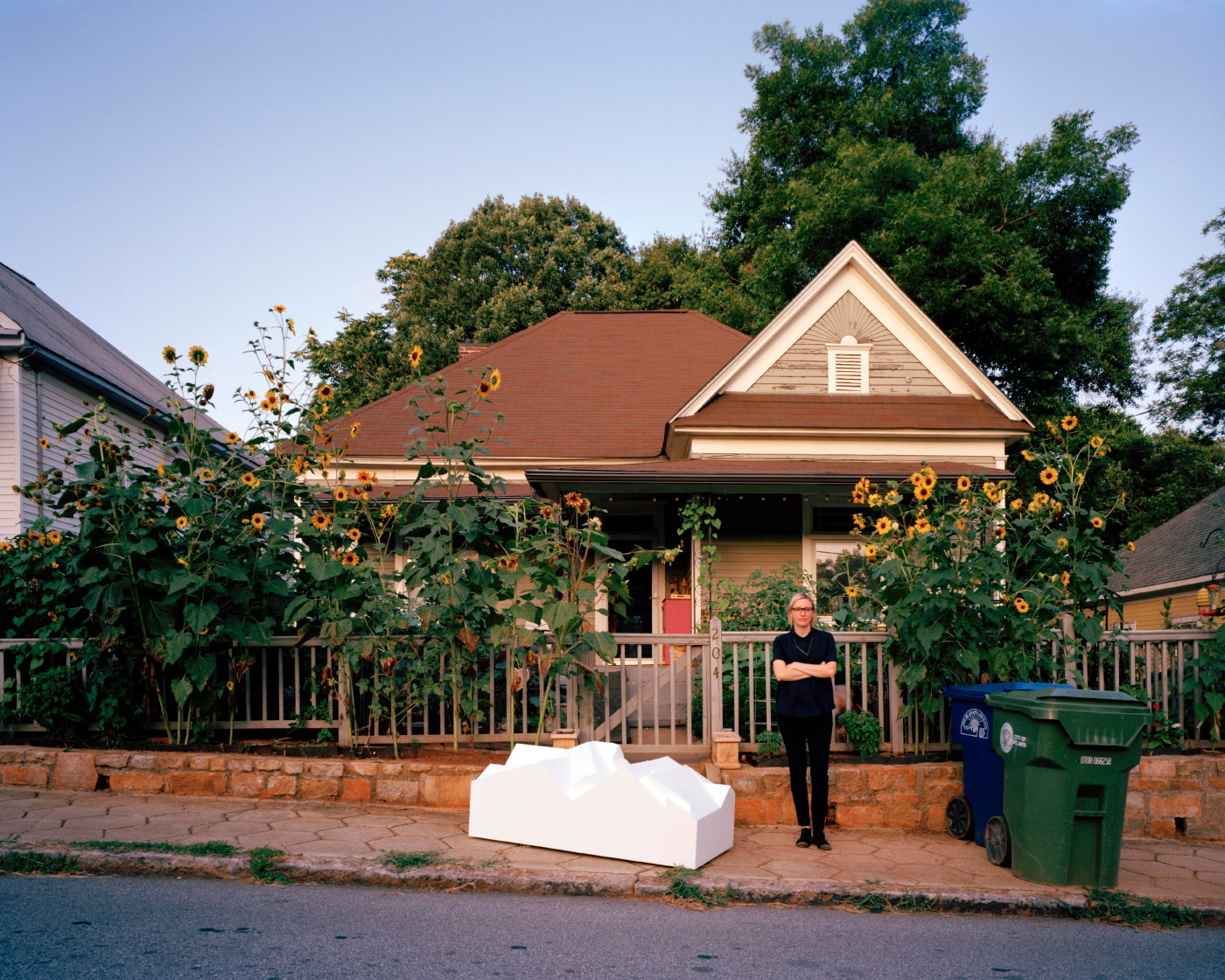 A photo of Jennifer Bonner and a gabled housing model on the sidewalk