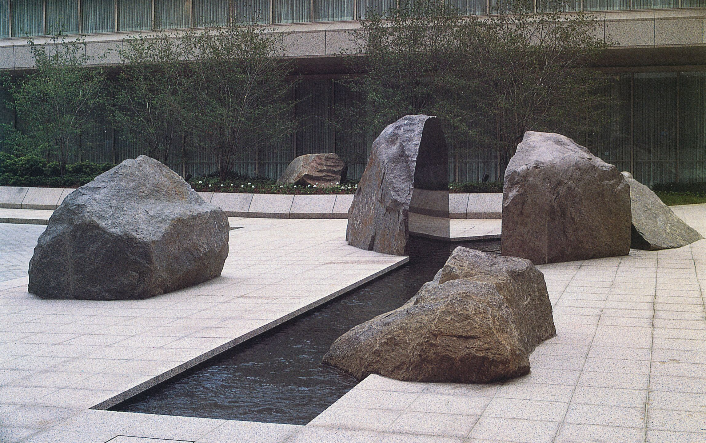 Exterior photo of the Marabar sculpture, split granite rocks, in a modernist courtyard