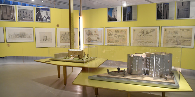 Interior of a gallery space with yellow walls and architectural drawings