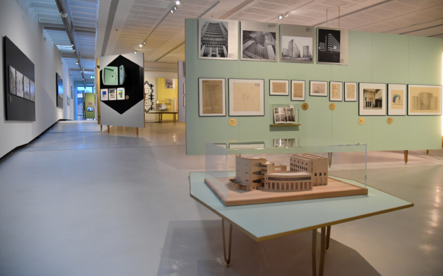 Interior wide shot of a gallery with architectural models on a table