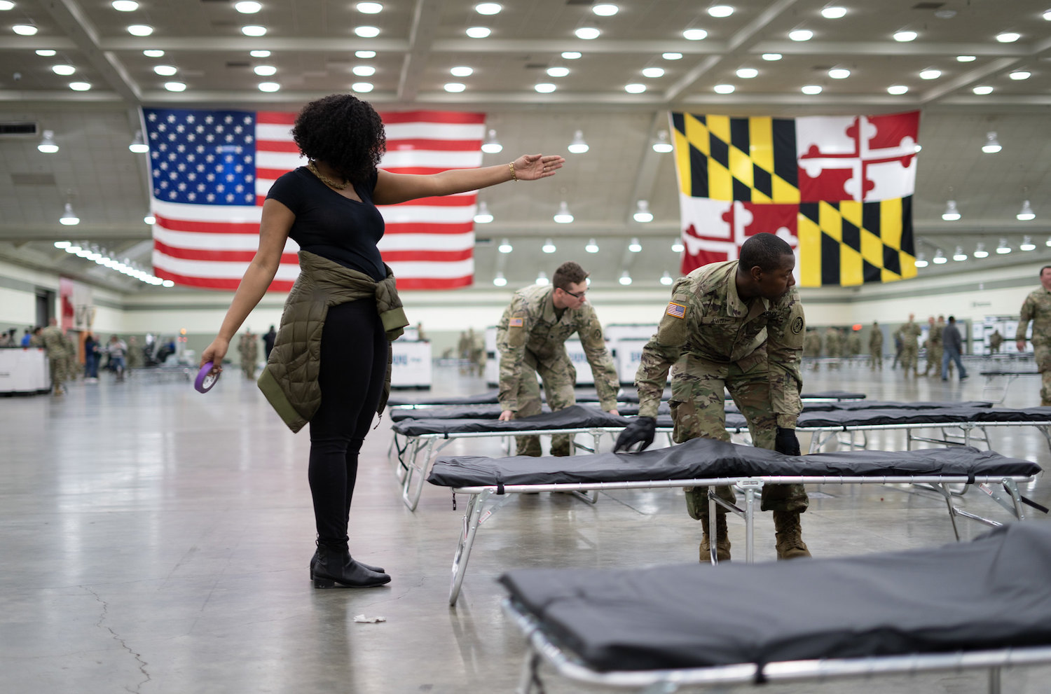civilans and national guard set up a hospital bed in a convention center as part of COVID-19 management