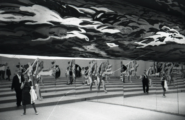 Black and white photo of people gathered beneath murals