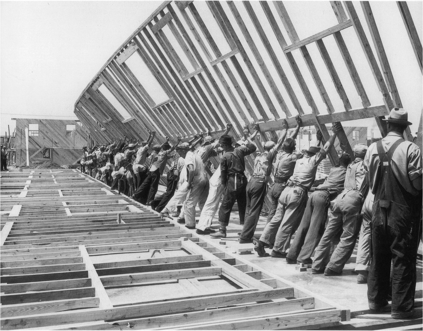 Black and white photo of men working together to raise a wood frame