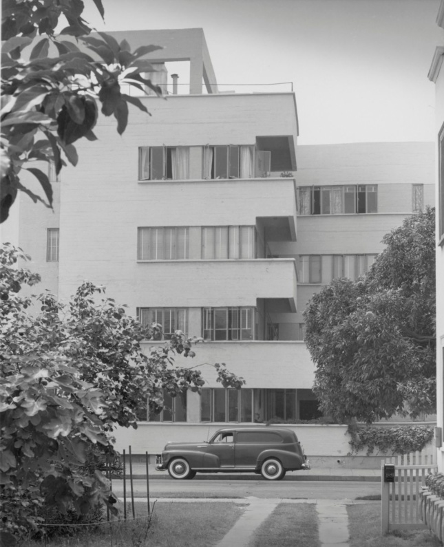 A tall white building and a car