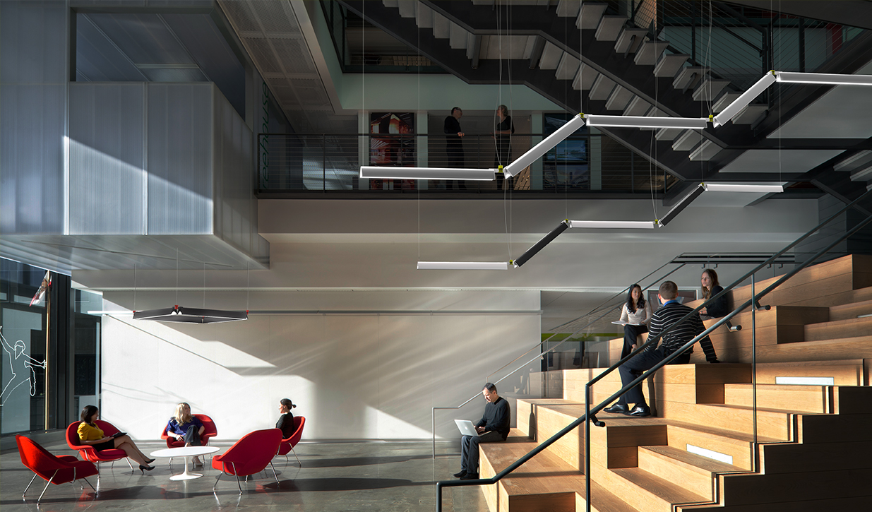 Interior of a multi-tiered office space with sittable stairs and modular lighting