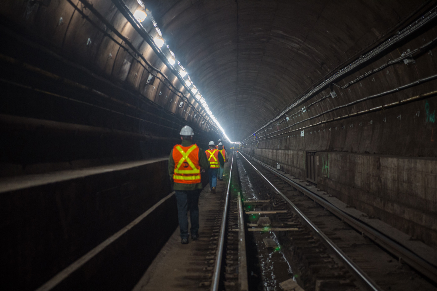 Construction workers walking through the L Train tunnel