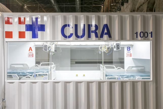 a container-based intensive care pod in italy, with a sign that says CURA
