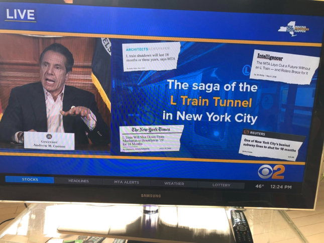 Andrew Cuomo presenting a slide with an AN article on it