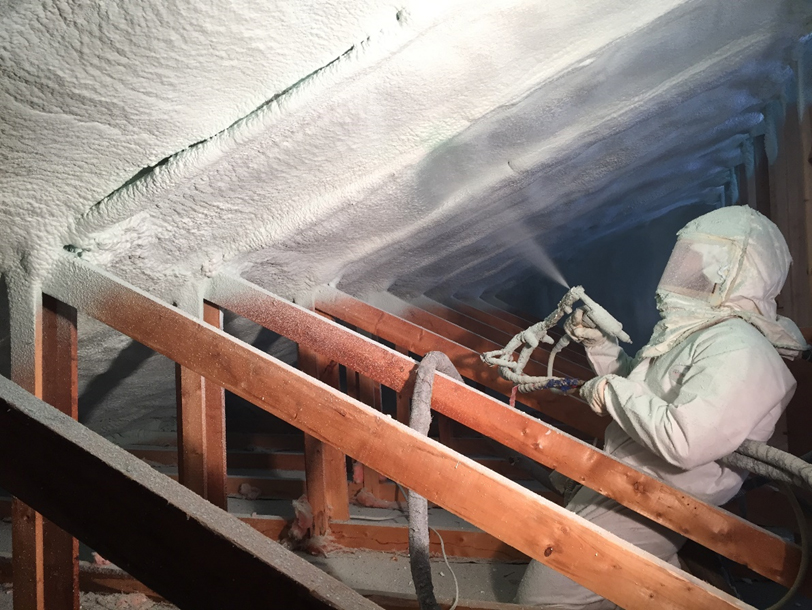 A man spraying Demilec insulation inside of a house
