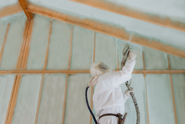 A man spraying insulation in a house