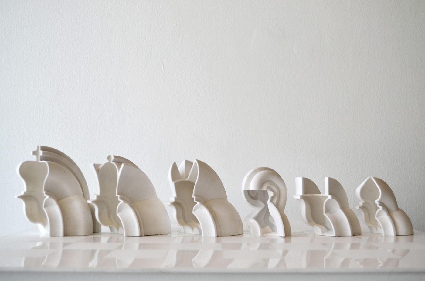 White, highly-designed chess set with curved pieces designed by Spinagu