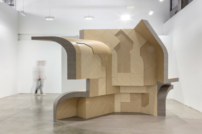Interior of a white gallery with a large wooden structure in the center