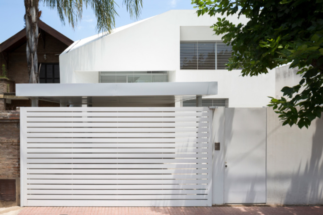 Exterior of a white home with vertically-oriented slits on the facade